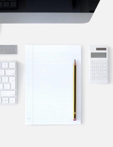 Blocco note Pillow Pad a righe in uso sulla scrivania con matita poggiata